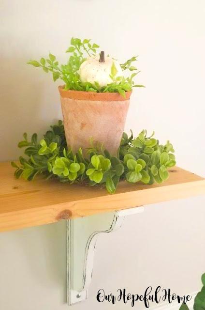 clay terra cotta pots green wreath white pumpkin dining room shelf