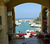 A view through an archway of boats in Portomaso Marina, Malta.