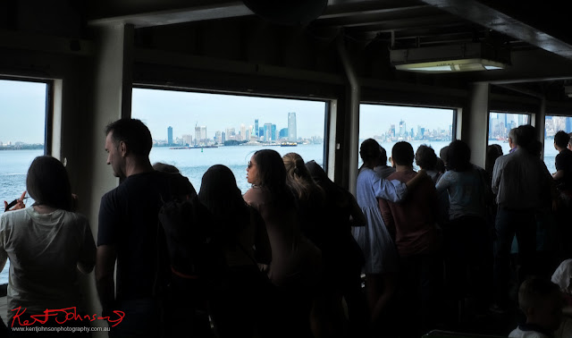 Travellers and commuters line the railings of the Staten Island Ferry for a view of the city skyline on the return trip to Manhattan. Travel photography by Kent Johnson.