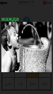 Мальчик пьет воду из фонтанчика в жару, открыл рот и ловит струю