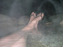 Feet crossed and relaxed, soaking in the natural creek hot springs.