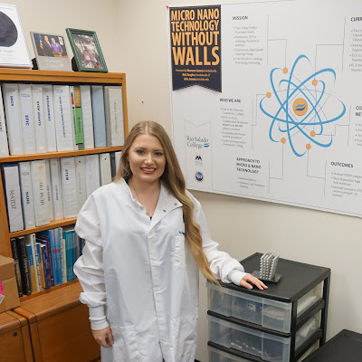 Photo of Rio Salado grad, Caitlan McGough in a lab coat, standing in front of a large poster mapping out Rio Salado's Nanotech program's mission, outcomes and the like.