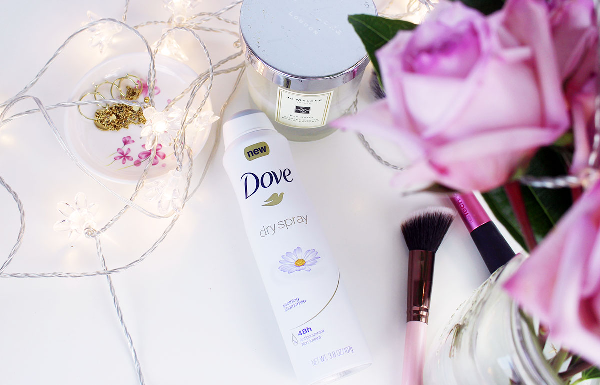 This is a close-up photo of the Dove Dry Spray Antiperspirant and my desk decorated with lights, and other makeup pieces.