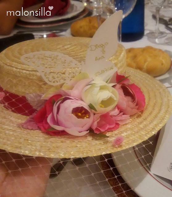 Canotier con flores rosas y tarjeta de boda en forma de mariposa