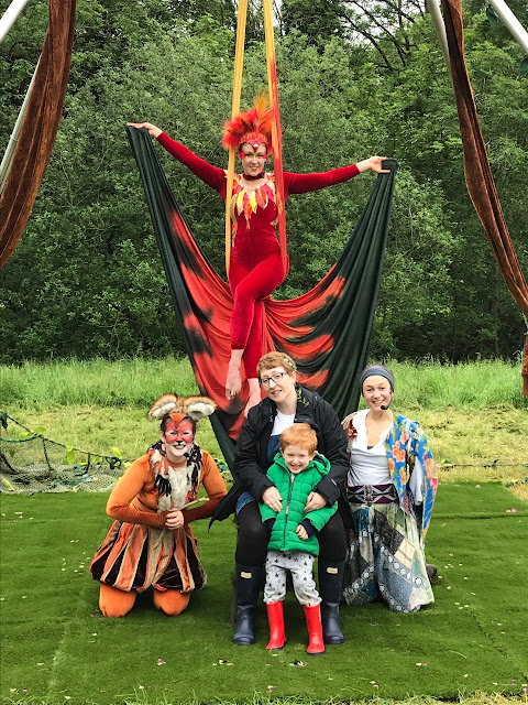 Mother and son, sitting with entertainers dressed as a thief, fox and phoenix