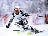 Hızla kayan bir kayakçı bir slalom bayrağından dönerken