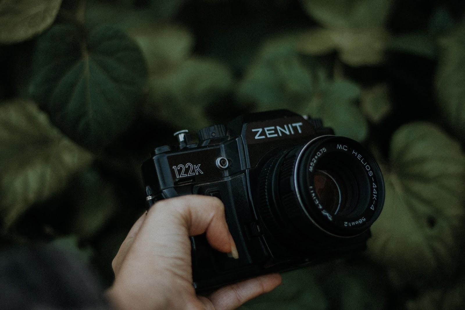 Comprei: Zenit 122. A Zenit 122 tem um fotômetro TTL que funciona por bateria. Esse fotômetro é feito por umas luzinhas que acendem no visor para indicar se a fotometria está errada ou certa.  Mas, eu não testei ainda se está funcionando. Eu tenho um medo que mesmo com a bateria nova, o fotometro não seja confiável. É que pelas câmeras serem antigas na maioria das vezes o fotometro não está com a regulação certa.