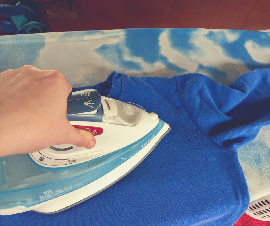A close up of an iron being used on a blue jumper. An example of #mumwinning.