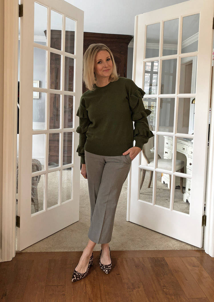 olive ruffle sweater with gray pants and leopard heels