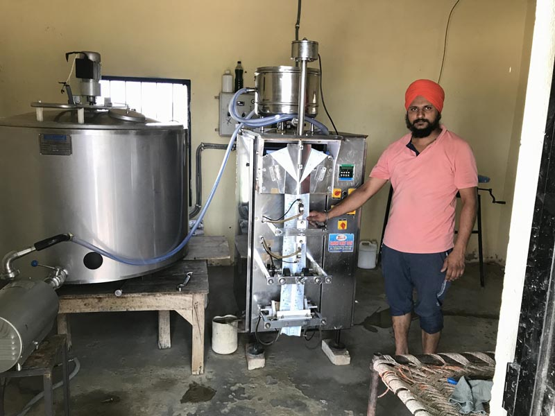 Dairy Farmer Sukhwinder singh explaining about the milk packaging machine installed at his farm