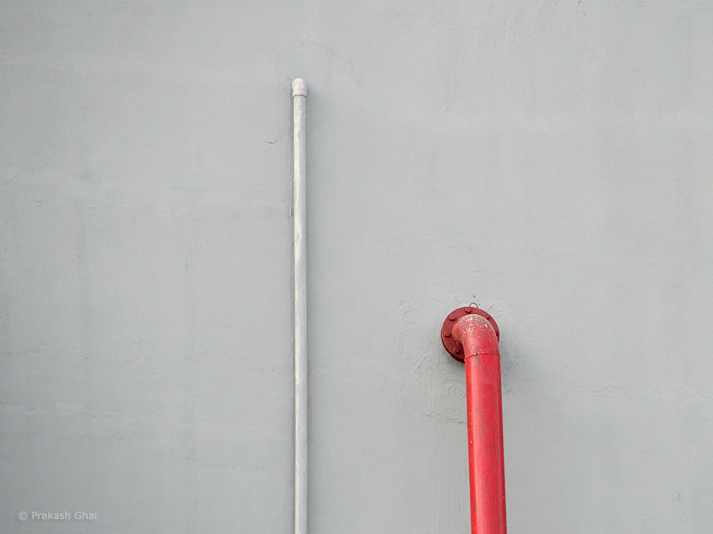 A Minimalist Photo of Red and gray steel water pipe on a gray wall.