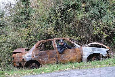 un homme (Douglas Carnall) portant la tenue de cycliste prend le volant d'une voiture brûlée