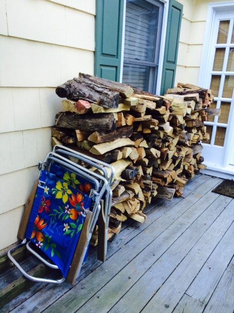 rack of cut firewood contrasted with beach chairs on wooden porch