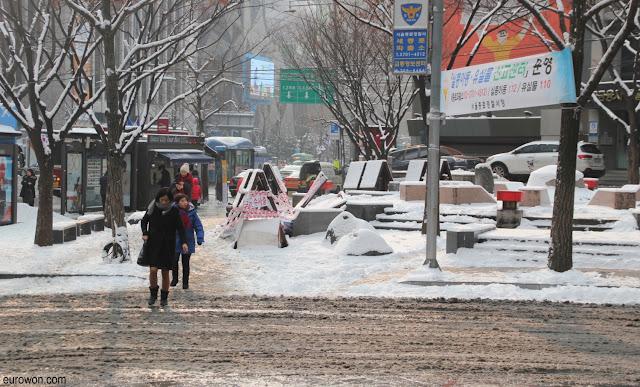 Personas cruzando una calle nevada en Seúl