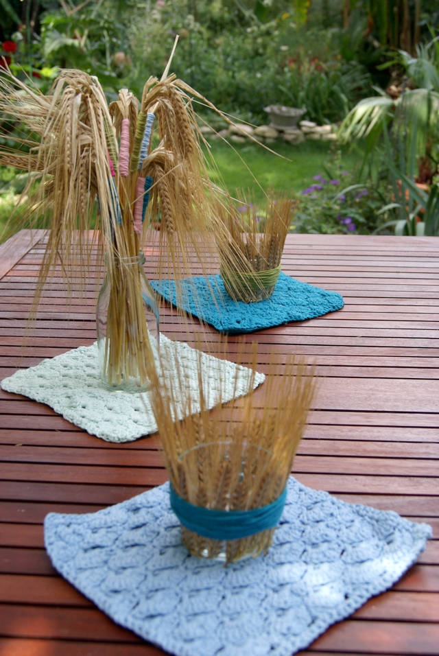 Teelichtgläser mit Ähren Wolle umwickelt und Häkeldecke