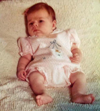 image of me as a baby, lying on my back and looking at something off-camera with a knitted brow