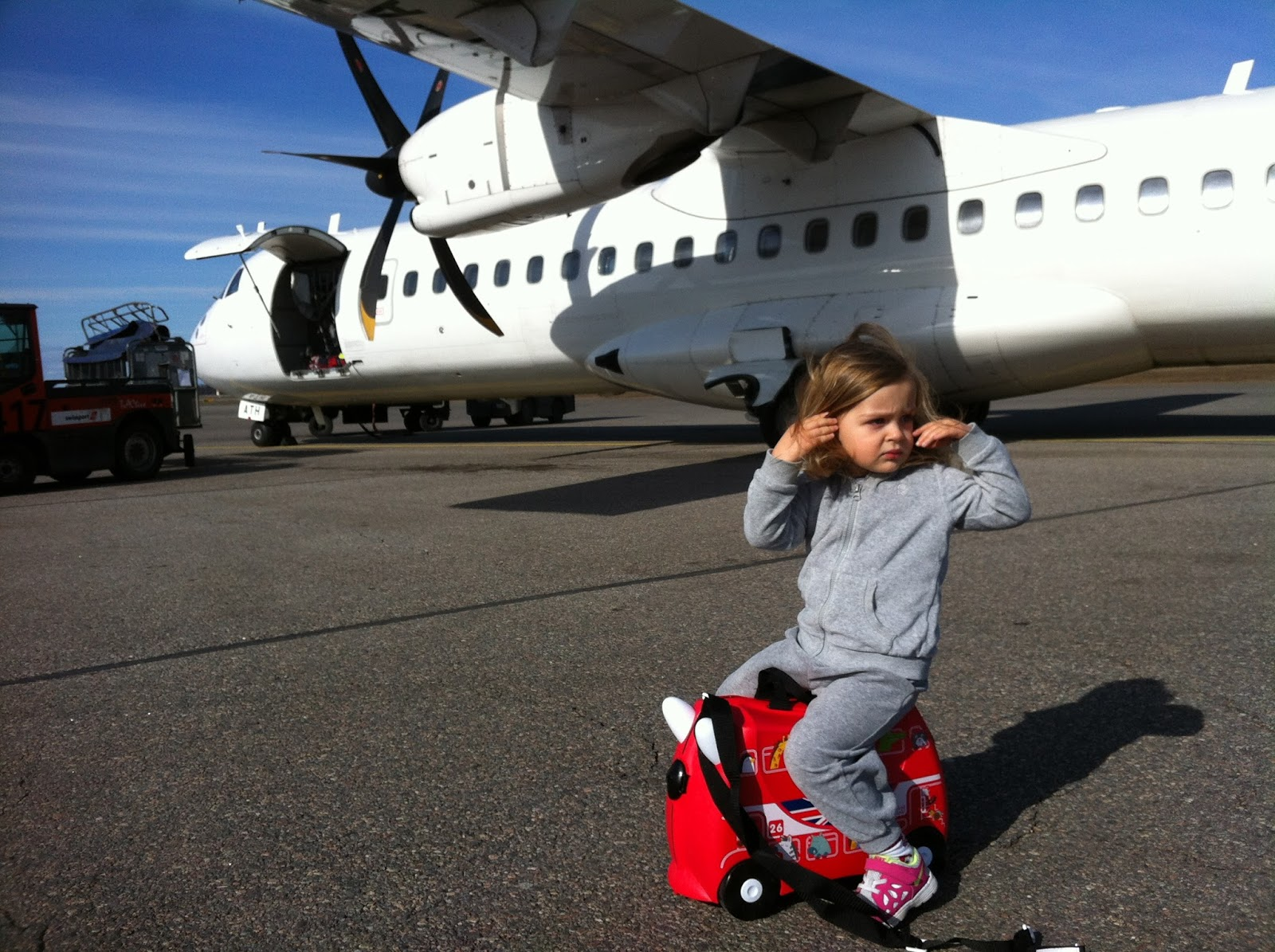 toddler sitting on trunki suitcase in front of a plane