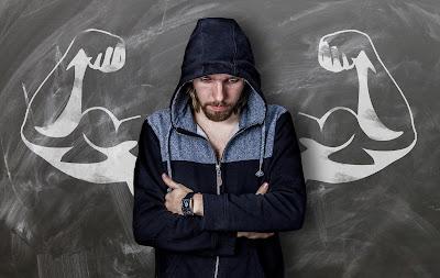 weak man standing front of wall