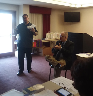 Rev Giovanni Arroyo reads a report, Rev. Leo Yates offers ASL interpretation