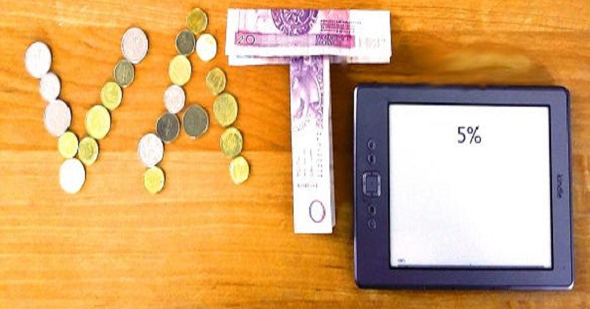 Napis VAT ułożony z monet i 5% na ekranie czytnika Kindle 4
