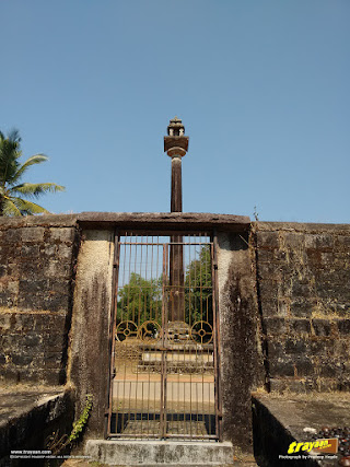 Neminatha temple's Manasthamba, a towering pillar, as seen from the small north gateway to the temple enclosure