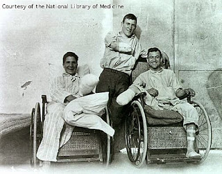 Black and white photo of three men with disabilities, two in wheelchairs two missing arms,