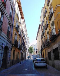 La estrecha calle tiene edificios de viviendas de tres plantas, con fachadas colores ocre y albero con los típicos balcones.