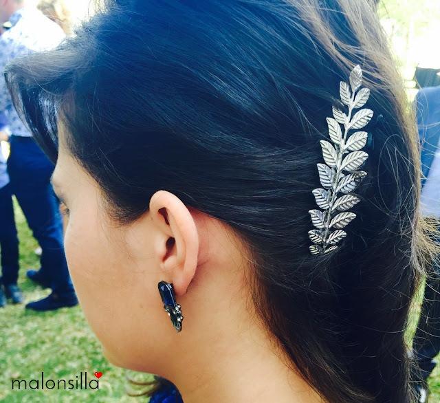 Invitada boda con peina tocado de hojas plateadas, su peinado es el pelo suelto moreno y ladeado, vestido azul klein lentejuelas