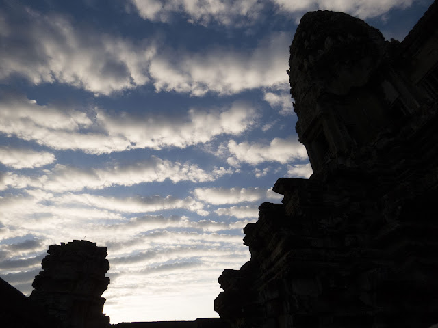 puffy white clouds just after sunrise over Angkor Wat in Cambodia