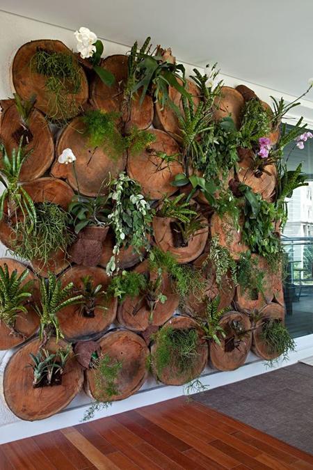 jardim vertical criado com rodelas de troncos como nichos para as plantas