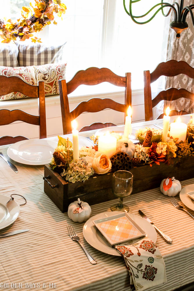 DIY wooden box centerpiece with flowers, pumkins and candles in fall dining room