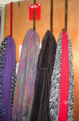 scarves hanging from wreath hangers on the back of a door