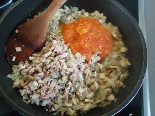 Elaboración de sofrito con cebolla, setas, conejo y tomate