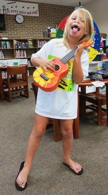 Young Avondale Library patron strums ukulele