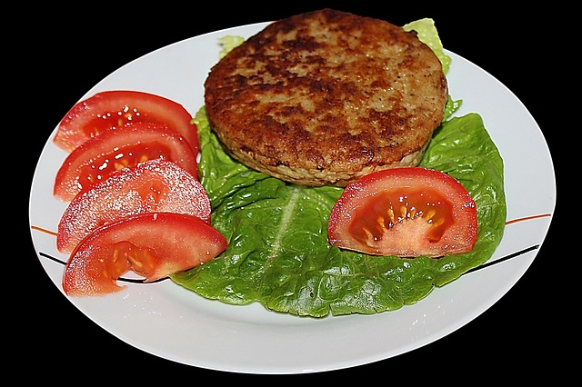 Ground Turkey Burger on Lettuce with a Wedged Tomato