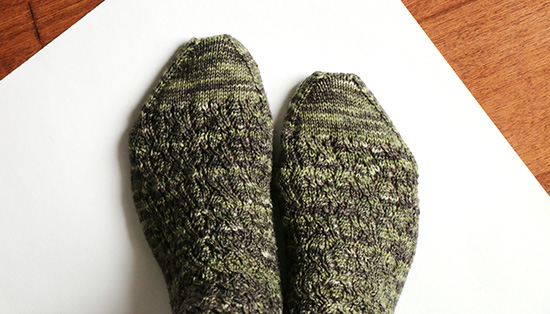 Top view of feet wearing dark green hand-knit socks on white background