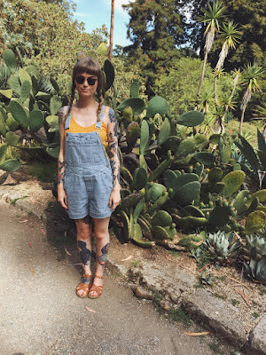 A picture of a tattooed woman in front of a prickly pear cactus plant in Golden Gate Park, San Francisco
