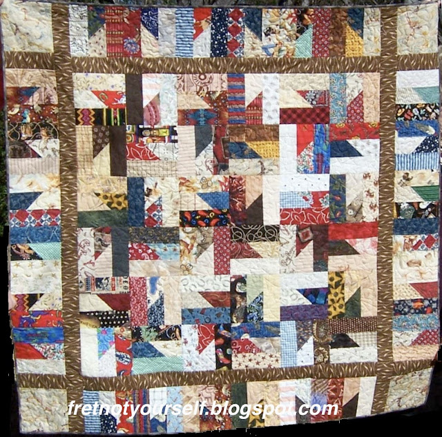 Western-themed fabric is used to create a baby quilt in red, black, brown, blue, tan and white.