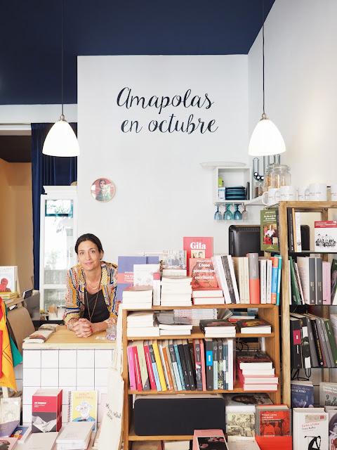 La escritora Laura Riñón en un mostrador con libros en su librería