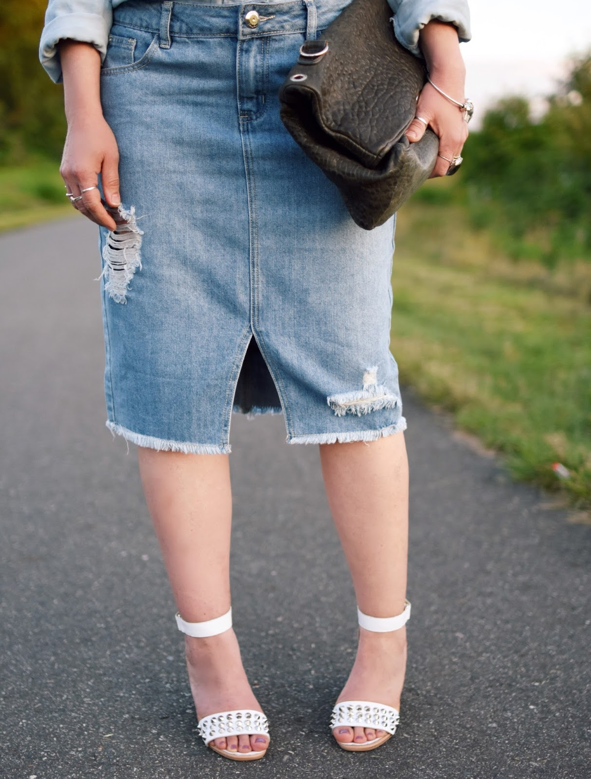 styling a distressed denim pencil skirt with a chambray shirt, studded ankle-strap sandals, and leather satchel