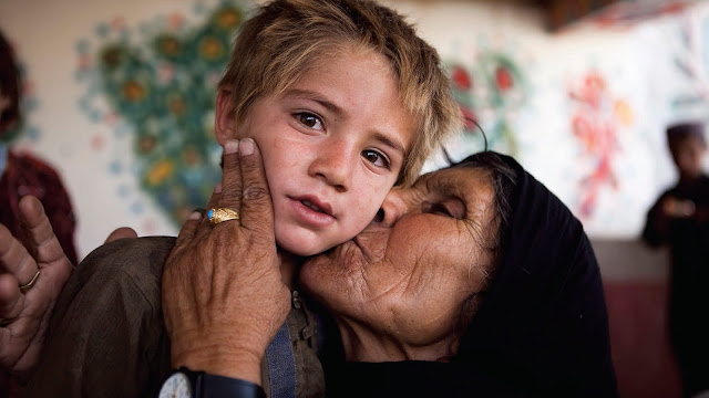 Photographic image of an old woman kissing young boy on a cheek