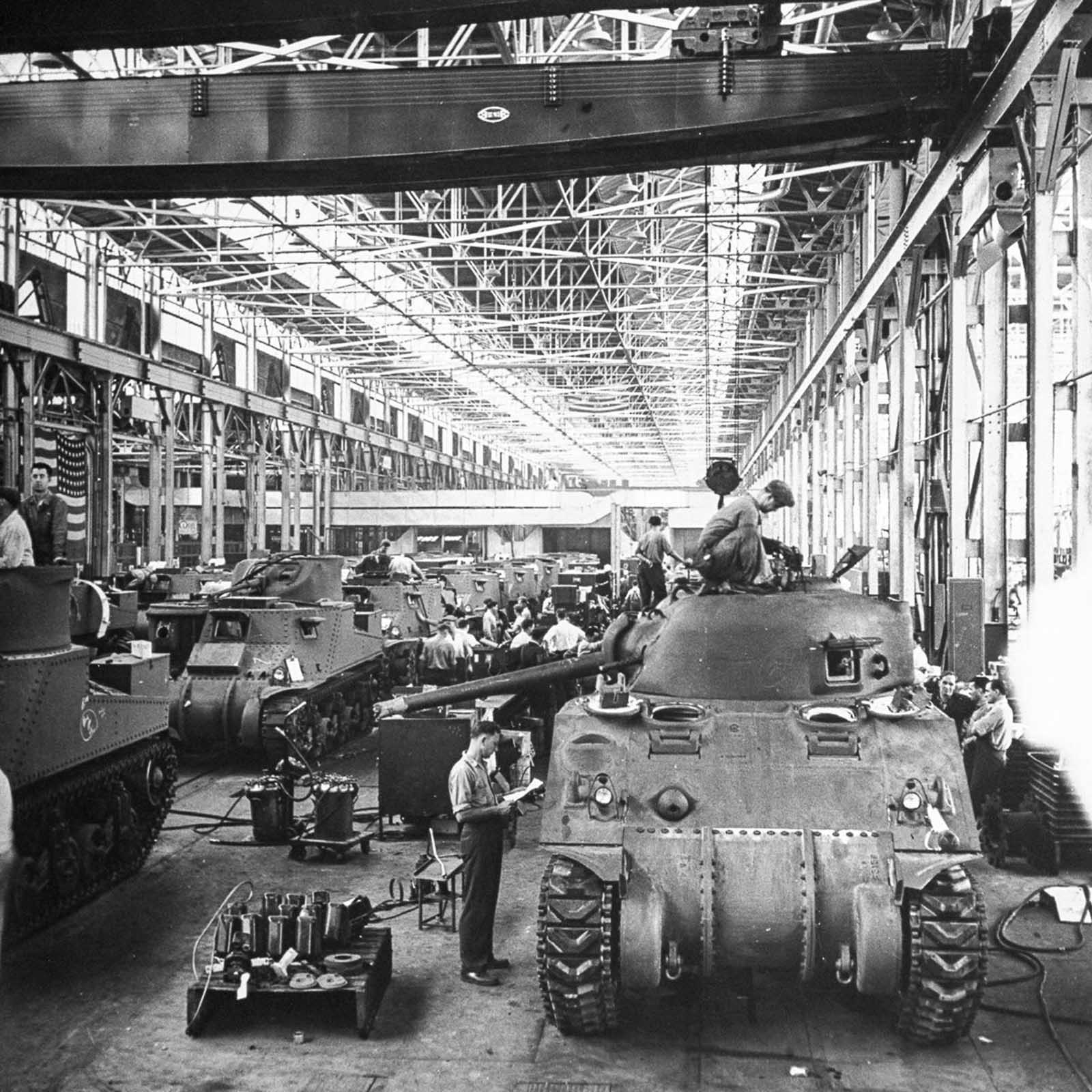 The assembly line at the Chrysler tank arsenal in Michigan changes over from M3 to M4 models while the line continues moving. 1942.