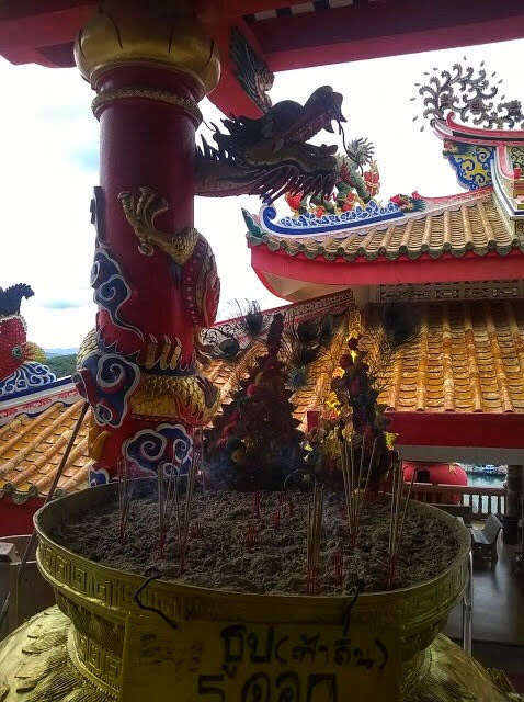 dragon motifs at a Chinese temple in Thailand with incense burning