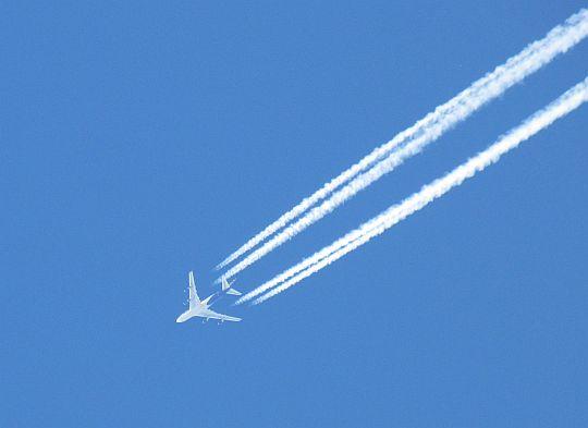 Błękit nieba przecina przelatujący samolot.