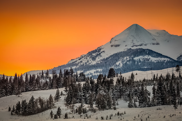 Antler Peak covered in snow with a tangerine colored sky