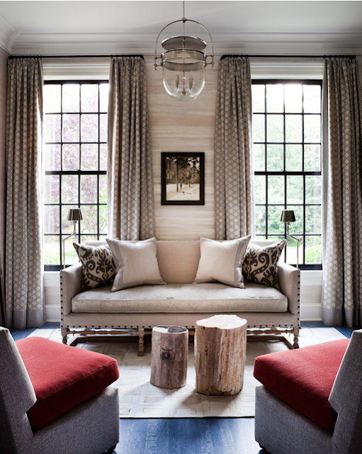 cozy seating area with uphlstered sitting and curtains.  red pillows seat on side chairs