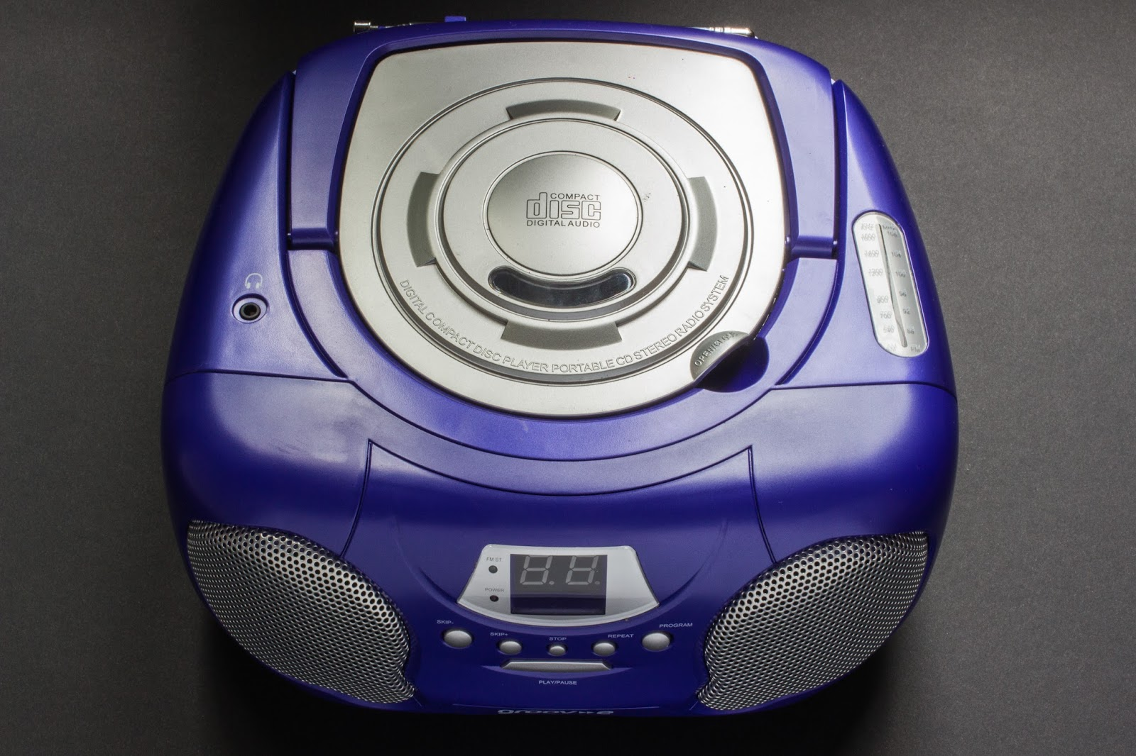 Purple stereo with 2 speakers and a cd player opening on top