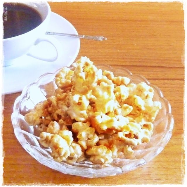 bowl of buttered popcorn and a coffee