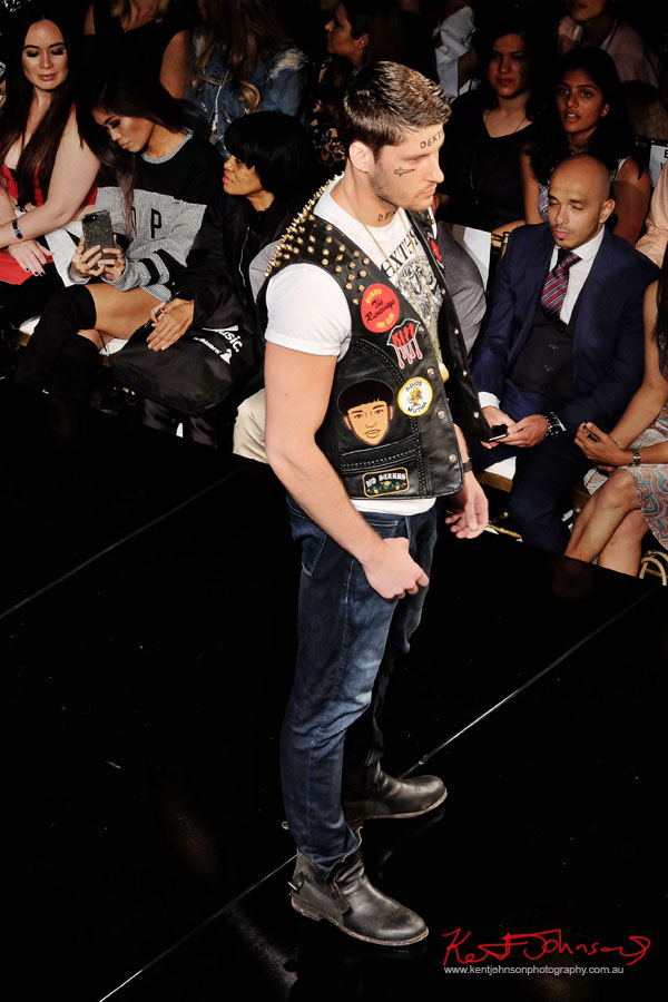menswear - Leather vest heavily embellished with studs and embroidered pop culture patches worn over white graphic tee shirt and jeans. Dexter Simmons at Art Hearts Fashion NYFW 2017 photographed by Kent Johnson.