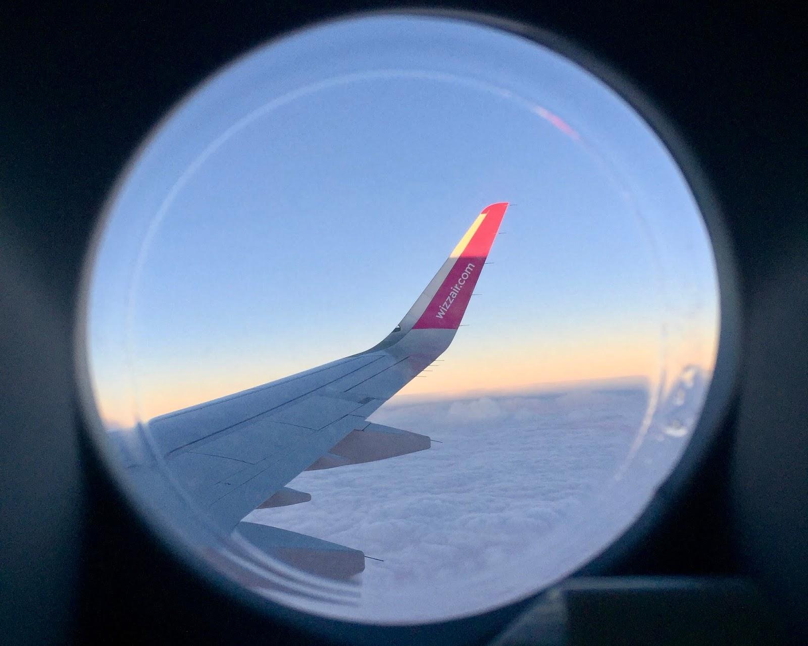 Křídlo letadla WizzAir ve vzduchu při východu slunce